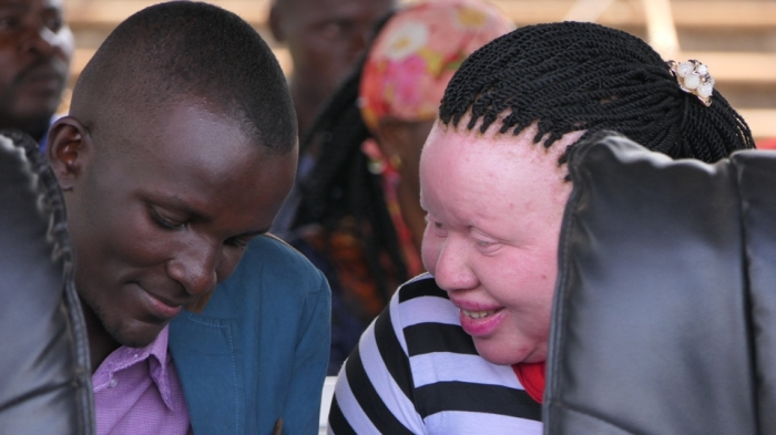 Allan Tenya Director GOBS Foundation speaks to a woman with albinism to see how they can work together in getting children with albinism back to school
