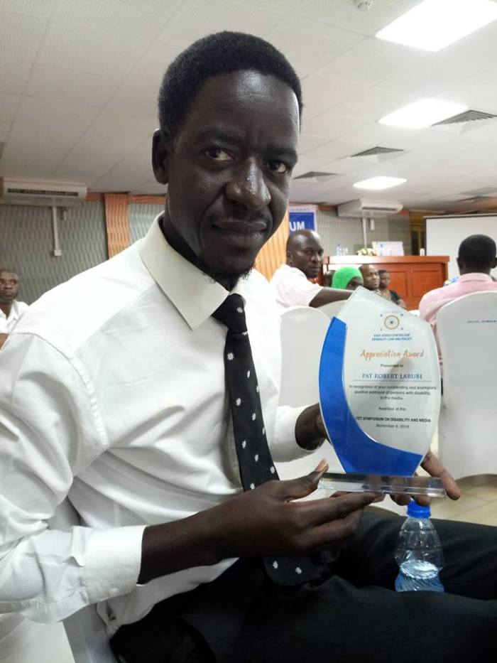 Pat displays his accolade for best reporting on disability inclusion in Uganda